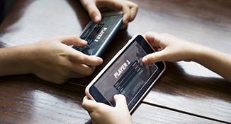 Image of two people competing on mobile games
